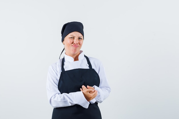 여성 요리사 유니폼, 앞치마에 푹 손을 잡고 불만을 찾고. 전면보기.