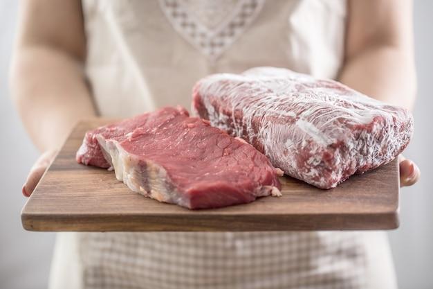 Женский повар держит деревянную доску сырого и замороженного мяса говядины.