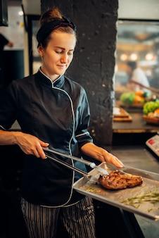 여성 요리사는 신선한 준비된 스테이크, 구운 고기를 보유하고 있습니다. 비프 스테이크 요리, 주방에서 음식 준비
