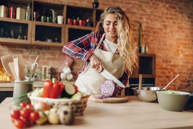 新鮮な野菜を切るエプロンで女性料理人