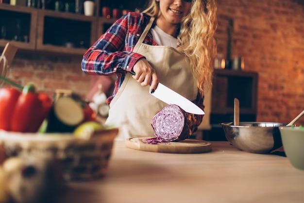 Женский повар в фартуке, режущий свежие овощи