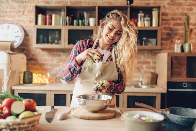 エプロンの女性料理人が新鮮なサラダを準備します