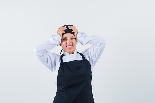 Женщина-повар в форме, фартук, взявшись за голову и забывчивый, вид спереди.
