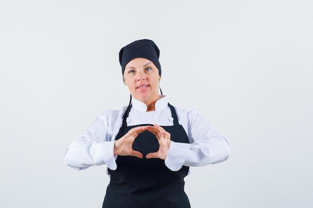 制服を着た女性料理人、手で形を作り、自信を持って見えるエプロン、正面図。