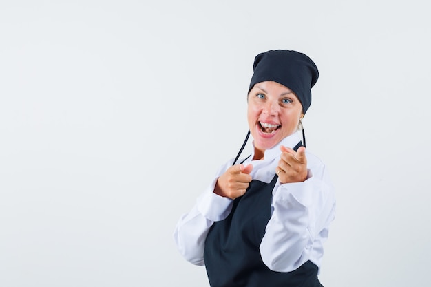 制服を着た女性料理人、カメラを指して幸せそうに見えるエプロン、正面図。
