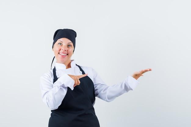제복을 입은 여성 요리사, 그녀의 손바닥을 가리키는 앞치마가 옆으로 펼쳐져 자신감, 전면보기를 찾고 있습니다.