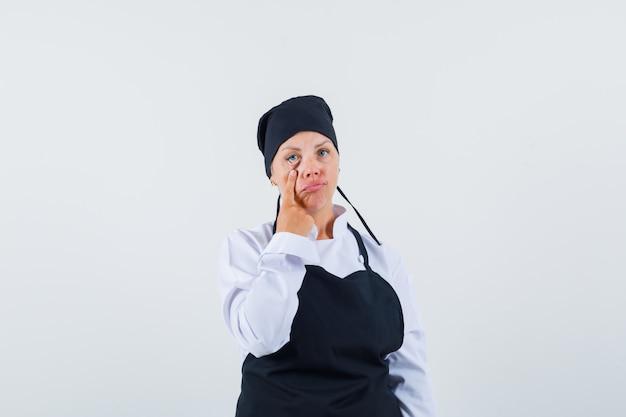 Женщина-повар в униформе, в фартуке задергивает веко и выглядит измученной, вид спереди.
