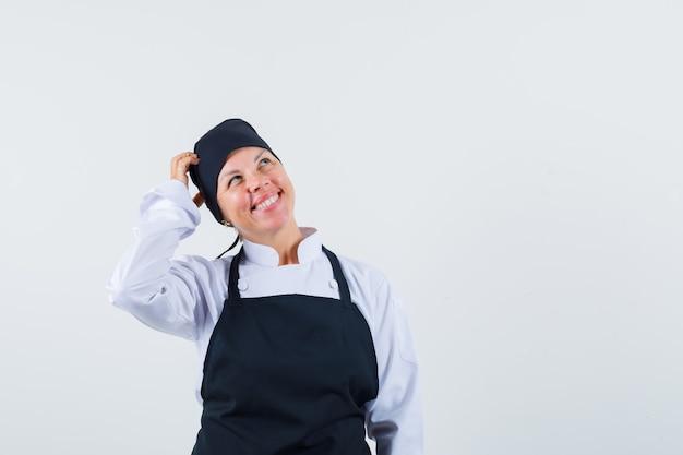 Женщина-повар в униформе, почесывает голову в фартуке и выглядит веселой, вид спереди.