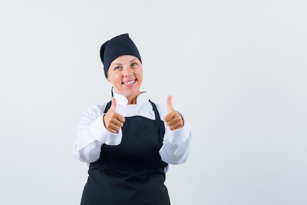 制服を着た女性料理人、二重親指を上に向けて陽気に見えるエプロン、正面図。