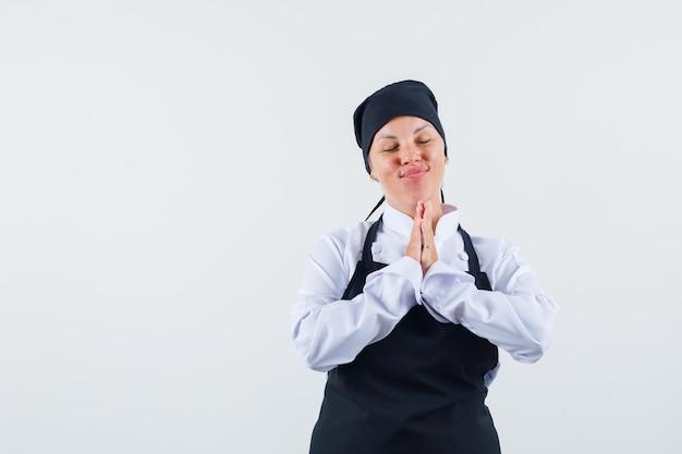 Женщина-повар в униформе, фартук показывает жест намасте и выглядит мирно, вид спереди.