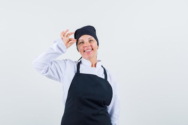 Женщина-повар в униформе, фартук, показывающий жест ок и веселый вид спереди.