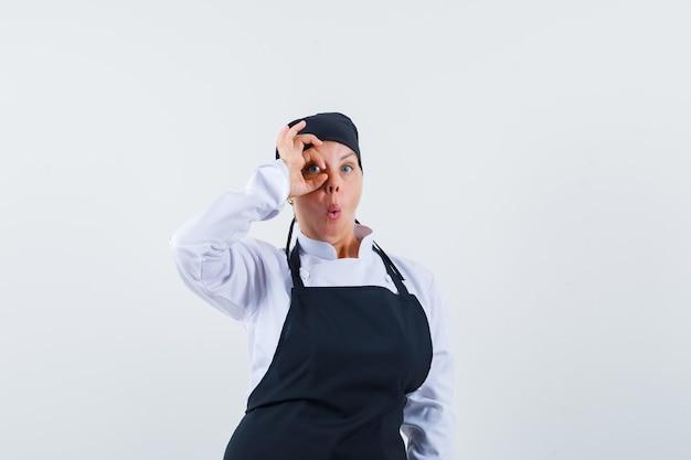 制服を着た女性の料理人、エプロンは目にokのサインを示し、驚いて見える、正面図。