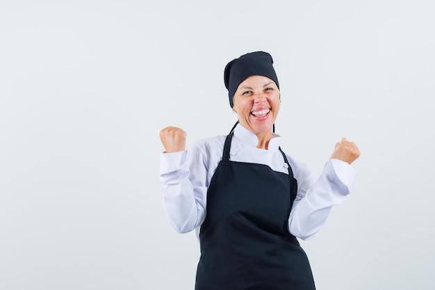 Женщина-повар в форме, фартук, показывающий жест победителя и блаженный вид спереди.