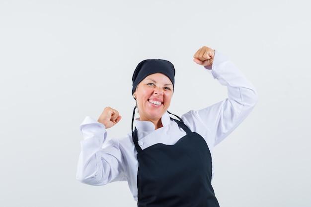 制服を着た女性料理人、勝者のジェスチャーを示し、至福の正面図を示すエプロン。