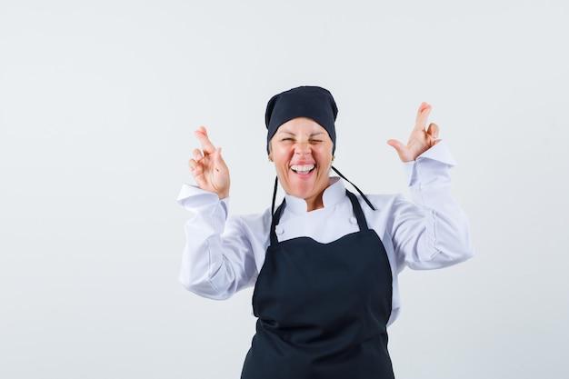 制服、エプロンで指を交差させ、至福のように見える女性料理人。正面図。