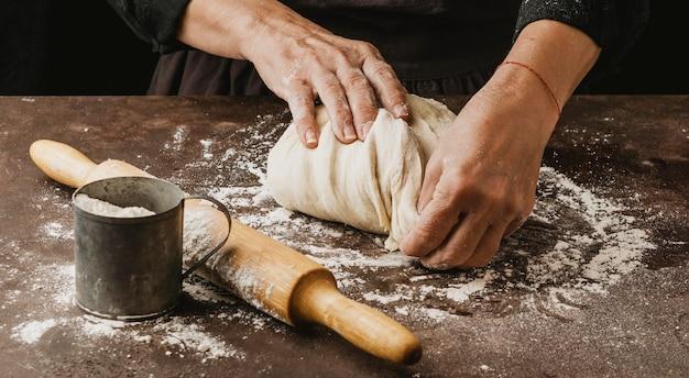 Cuoco femminile che impasta la pasta della pizza