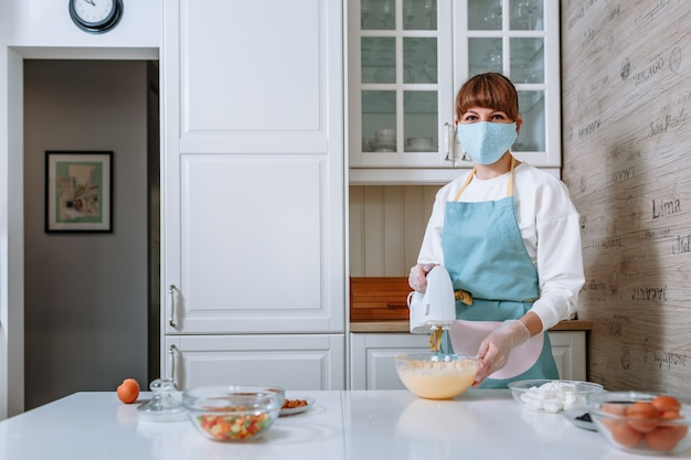 A female cook in a medical mask and gloves whips up cake batter