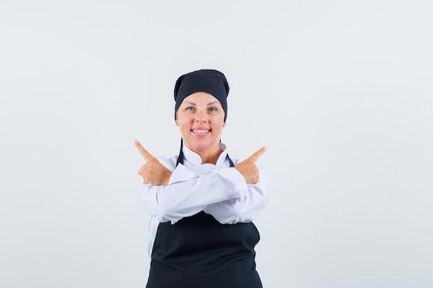 Женщина-повар указывая в сторону в униформе, фартуке и выглядит уверенно. передний план.