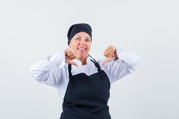 Female cook pointing at herself with thumbs in uniform, apron and looking proud , front view.