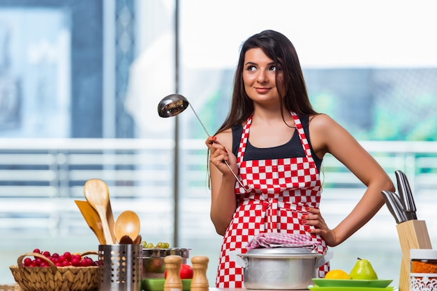 Female cook preparing soup in brightly lit kitchen