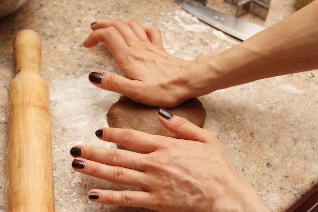 キッチンでクッキーを作るために生地を準備する女性料理人