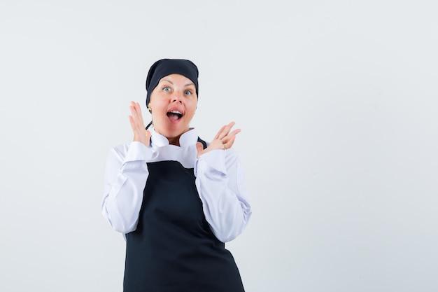 Женский повар поднимает руки в форме, фартуке и выглядит взволнованным. передний план.