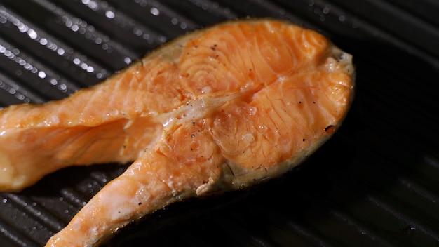 Женщина-повар заправляет стейки из лосося с черным перцем на гриле