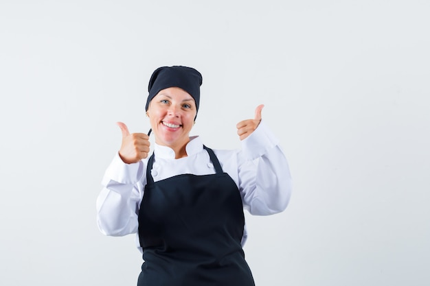 Female cook showing double thumbs up in uniform, apron and looking merry , front view.