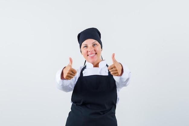 Cuoco femminile che mostra i doppi pollici in su in uniforme, grembiule e che sembra allegro, vista frontale.
