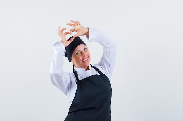 Cuoco femminile che mostra il gesto del cuore in uniforme, grembiule e che sembra felice. vista frontale.