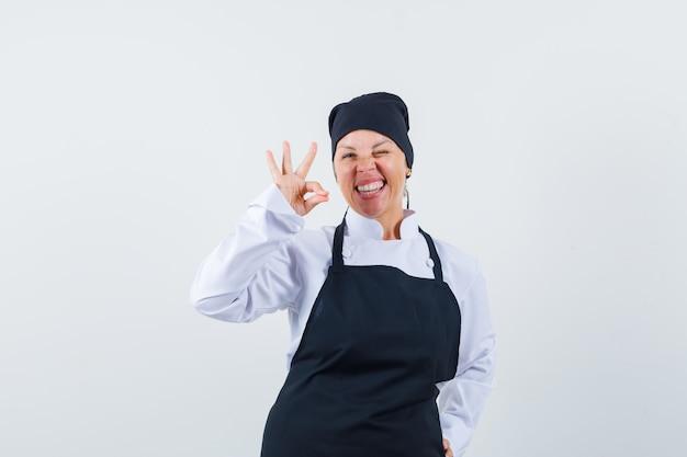 Повар-женщина показывает жест в униформе, фартуке и выглядит блаженно. передний план.