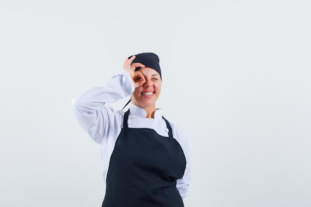 Женский повар показывает хорошо знаком на глаз в форме, фартуке и выглядит счастливым. передний план.