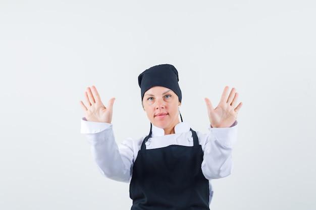 Повар-женщина показывает жест отказа в униформе, фартуке и выглядит уверенно, вид спереди.