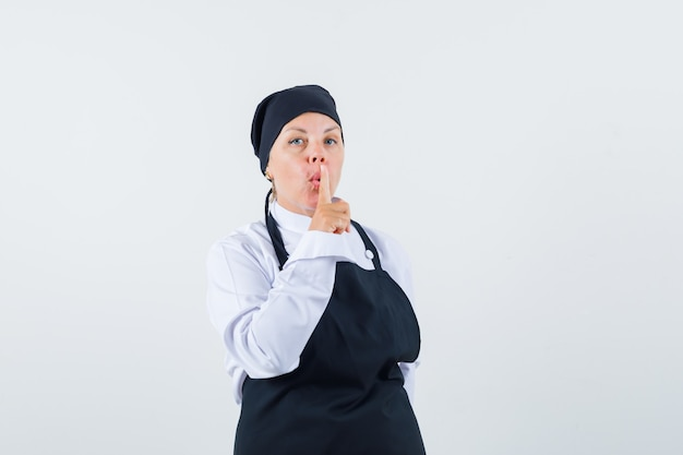 制服、エプロンで沈黙のジェスチャーを示し、注意深く見ている女性料理人、正面図。