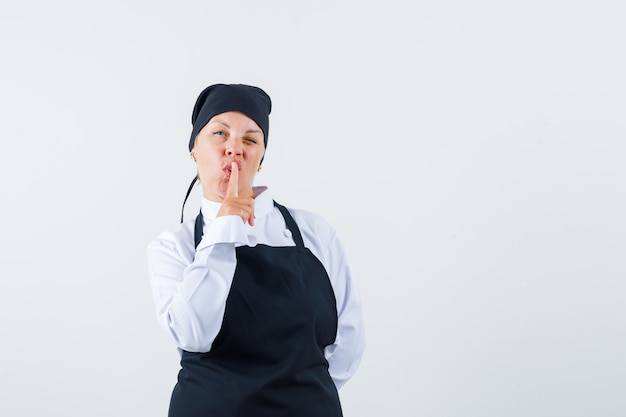 Повар-женщина показывает жест молчания в униформе, фартуке и выглядит уверенно. передний план.