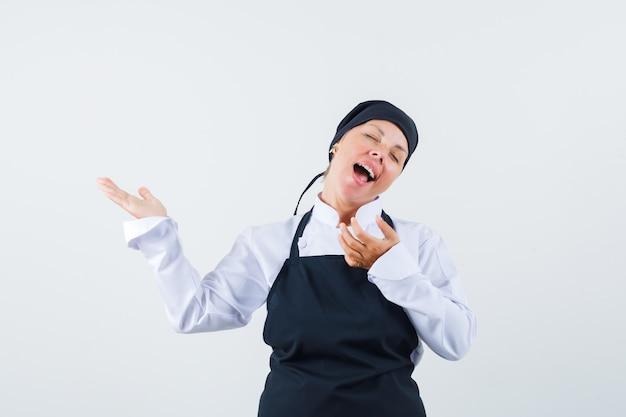 制服、エプロンで何かを見せて、狂ったように見える女性料理人、正面図。