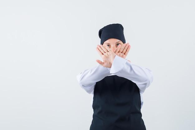 Женщина-повар показывает жест остановки в униформе, фартуке и выглядит серьезным, вид спереди.