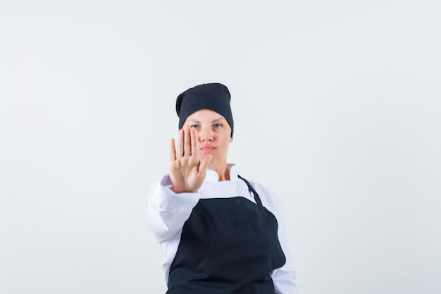 Female cook showing stop gesture in uniform, apron and looking confident. front view.