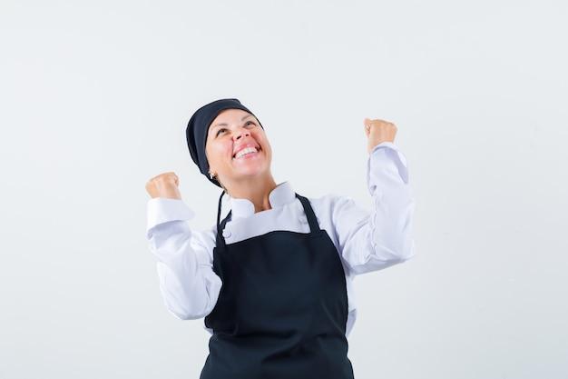 Повар-женщина показывает жест победителя в униформе, фартуке и выглядит удачливым. передний план.