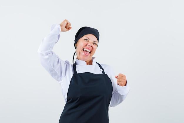 制服、エプロンで勝者のジェスチャーを示し、幸運に見える女性料理人。正面図。