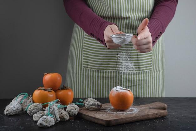 부엌에서 단감에 밀가루를 흘리는 여성 요리사