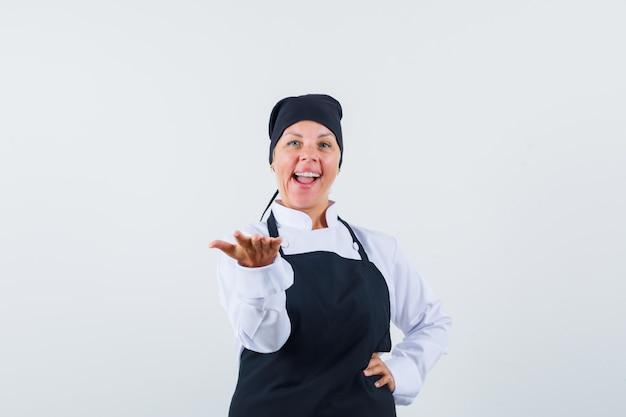 制服、エプロン、自信を持って、正面から何かを提示するように手を伸ばす女性料理人。