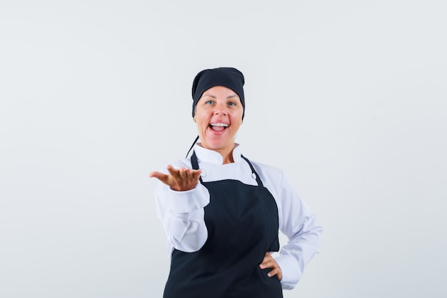 Female cook stretching hand as presenting something in uniform, apron and looking confident , front view.