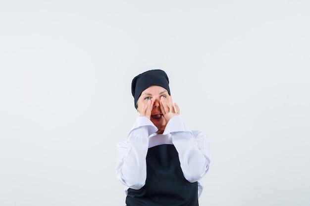 여성 요리사 유니폼, 앞치마 전면보기에서 입 근처 손으로 비밀을 말하고 있습니다.