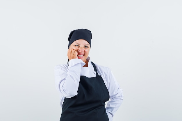 Female cook in uniform, apron holding hand on cheek and looking cute , front view.
