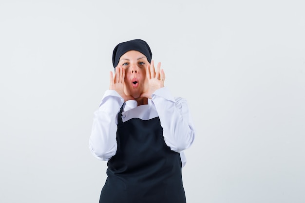 Female cook in uniform, apron holding hand near mouth while shouting , front view.