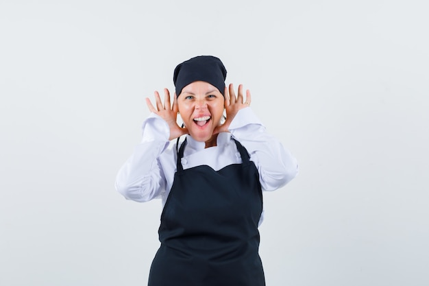 Female cook in uniform, apron holding hands near ears and looking crazy , front view.