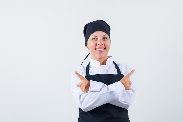 Female cook in uniform, apron pointing away and looking cheerful , front view.