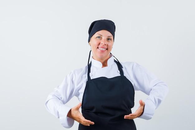 Cuoco femminile in uniforme, grembiule che finge di sollevare o tenere qualcosa e sembra fiducioso, vista frontale.