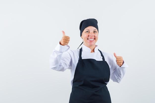 Cuoco femminile in uniforme, grembiule che mostra i doppi pollici in su e che sembra contento, vista frontale.